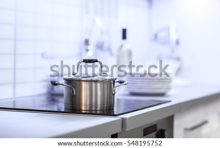 Metallic saucepan in modern kitchen interior