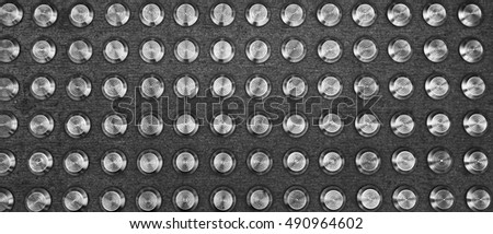 Metallic studs in concrete at a pedestrian crossing. Abstract background