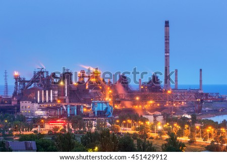 Metallurgical plant at night. Steel factory with smokestacks . Steelworks, iron works. Heavy industry in Europe. Air pollution from smokestacks, ecology problems. Industrial landscape at twilight - stock photo