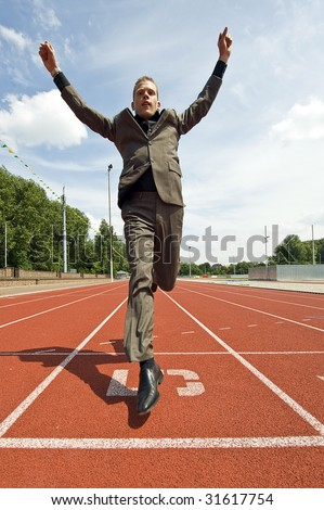 Metaphor for success in business - a business man crossing the finish line on an athletics track with his arms raised in victory - stock photo