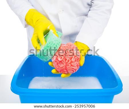 Metaphor of brainwashing, doctor washes the brain with the sponge. - stock photo