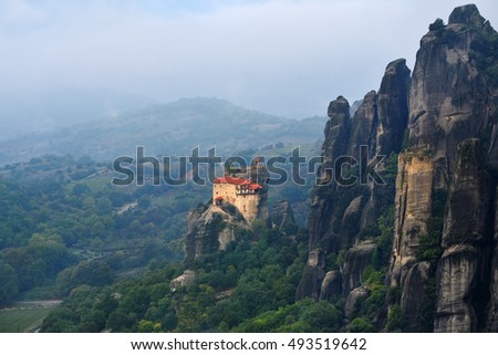 Meteora monasteries. Beautiful view on the Holy Monastery of St Nikolaos Anapafsas placed on the edge of high rock covered of the morning clouds and mist at sunrise, Kastraki, Greece