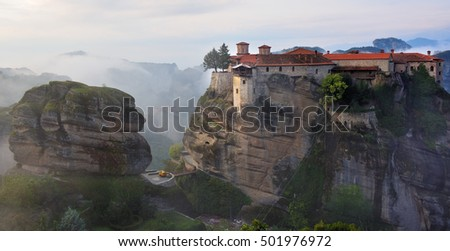 Meteora monasteries. Beautiful view on the Holy Monastery of Varlaam placed on the edge of high rock covered of the morning clouds and mist at sunrise, Kastraki, Greece.