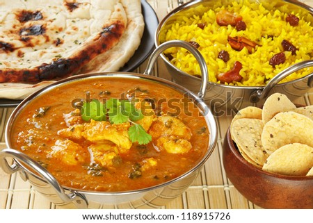 Methi Chicken, or Butter Chicken, with pillau rice, naan bread and poppadums. - stock photo
