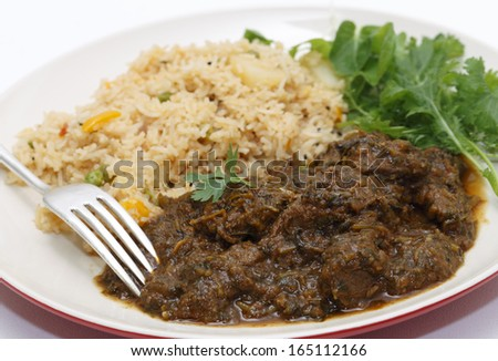 Methi gosht or fenugreek lamb, served with tomato (thakkali) biryani and a leafy salad, seen close-up