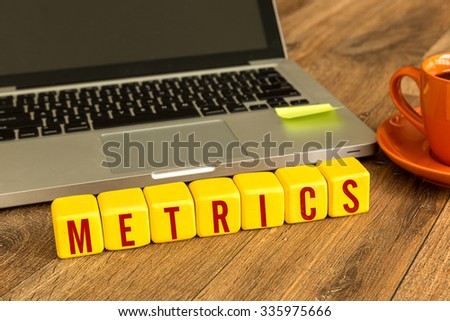 Metrics written on a wooden cube in front of a laptop - stock photo