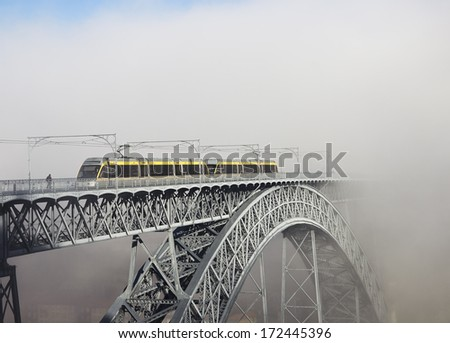 Metro Train on the Bridge Built by Eiffel in Porto, foggy morning - stock photo