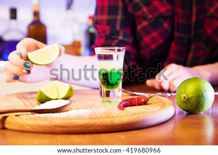 Mexican alcoholic cocktail drinks shot on a wooden board. Good tequila cocktail drinks, booze with decor composition with barman. Different layers of alcohol vodka, liqueur, chasers for drinks. - stock photo