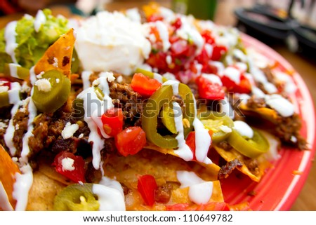 Mexican appetizer of nacho chips loaded with beef, cheese and jalapenos - stock photo