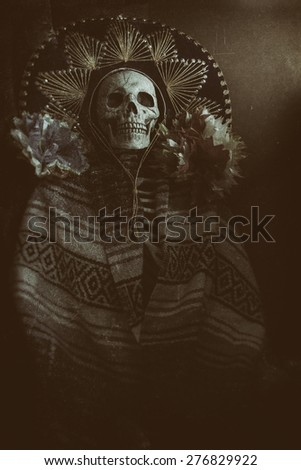 "Mexican Bandit Skeleton 5. A skeleton wearing a Mexican sombrero and a poncho, with decorative flowers in a ""Day of the Dead"" decor. Edited in a vintage film style. - stock photo"