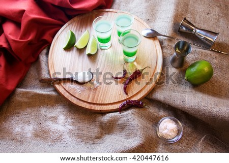 Mexican Bar alcoholic cocktail drinks shot on a wooden board. Good tequila drinks or booze with decor composition. Different layers of alcohol vodka, liqueur, whiskey chasers for drinks.  - stock photo