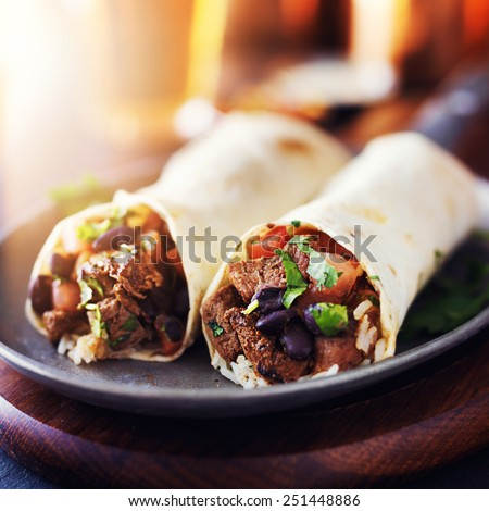 mexican beef steak burritos with black beans, rice, and salsa - stock photo