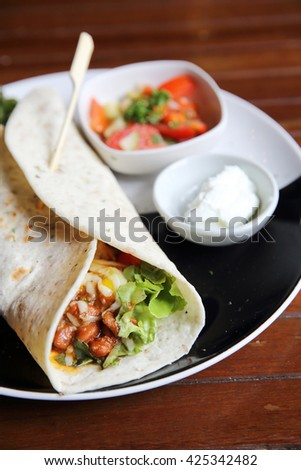 Mexican burritos on a plate with tomato salad
