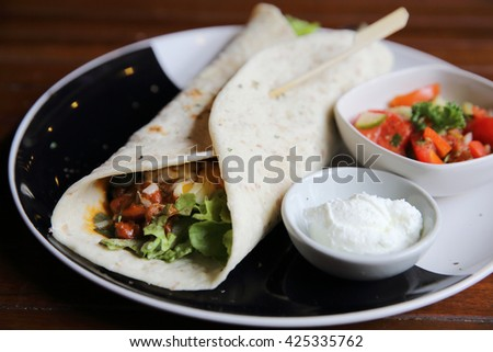 Mexican burritos on a plate with tomato salad , burritos