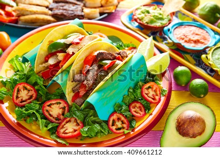 Mexican chicken and beef fajitas tacos in colorful table with sauce - stock photo