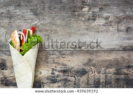 Mexican chicken fajita with peppers lettuce and onion on a rustic wooden table   - stock photo