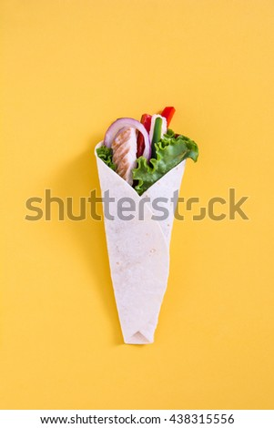Mexican chicken fajita with peppers lettuce and onion on yellow background   - stock photo