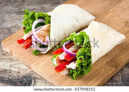 Mexican chicken fajitas with peppers lettuce and onion on a rustic wooden table   - stock photo