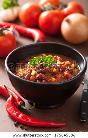 mexican chili con carne in black plate with ingredients - stock photo