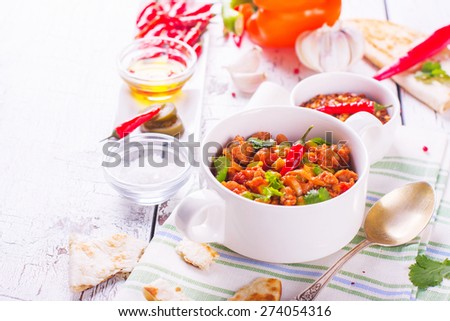 Mexican chili con carne with ingredients on white wooden table. Selective focus - stock photo