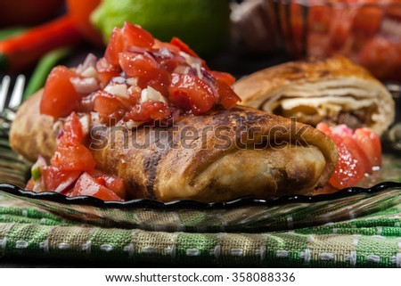 Mexican chimichanga with salsa dip on a plate