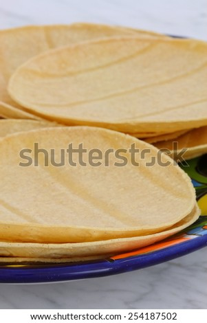 Mexican corn tortillas on retro vintage carrara marble in beautiful talavera plate, perfect for all your Mexican and tex-mex recipes. - stock photo