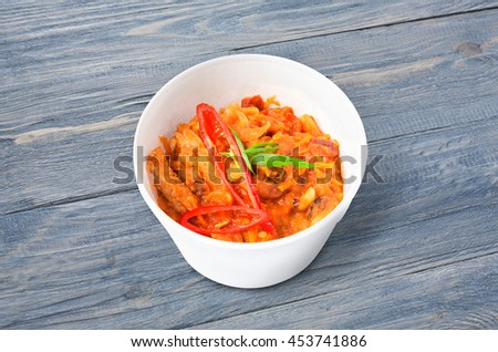 Mexican cuisine food delivery - chili con carne in white plastic plate closeup at rustic blue wood background - stock photo
