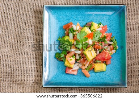 Mexican cuisine: Pico de Gallo.  The dish  is a fresh, uncooked salad made from chopped tomato, onion, cilantro, fresh serranos, salt, and key lime juice. Other ingredients may also be added. - stock photo