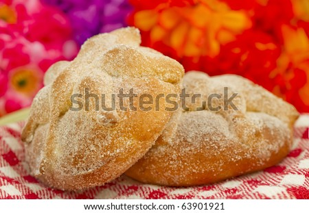 Mexican Day of the dead bread, Pan de Muerto, with flowery background.