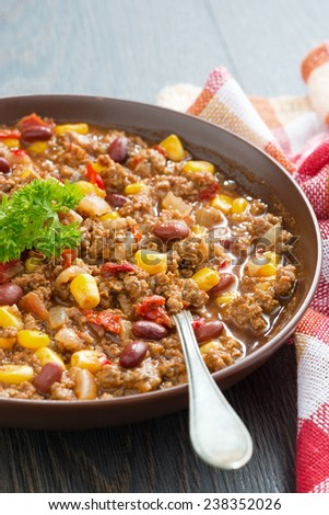 Mexican dish chili con carne in a brown pottery plate, vertical, close-up - stock photo