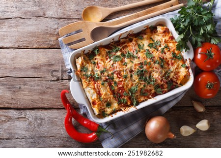 Mexican enchilada in a baking dish with the ingredients on the table. horizontal view from above  - stock photo