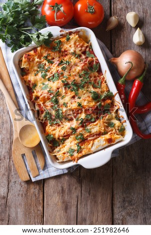 Mexican enchilada in a baking dish with the ingredients on the table. vertical view from above  - stock photo
