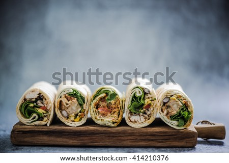 Mexican fajita wraps on serving board, copy space for text or menu - stock photo