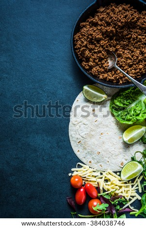 Mexican fajitas or tortillas, food border background with space for text or recipe. Overhead on dark slate. - stock photo