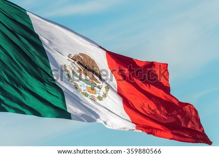 mexican flag weaving on sky background - stock photo