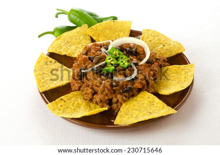 Mexican food: chili with meat served with nachos - stock photo