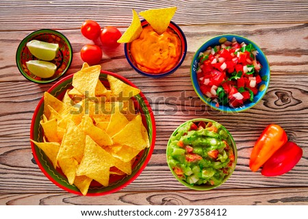 Mexican food mixed guacamole nachos chili sauce dipping cheddar cheese lemon pico de gallo - stock photo