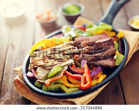 mexican food - skillet fajitas with steak and chicken on rustic wooden table - stock photo