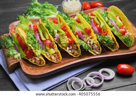 Mexican food tacos, peppers, cherry tomatoes, grated cheese, minced meat in a corn tortilla on a tray on a linen towel on a black wooden background - stock photo