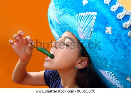 Mexican girl profile eating jalapeno hot chili pepper with blue mexican hat - stock photo