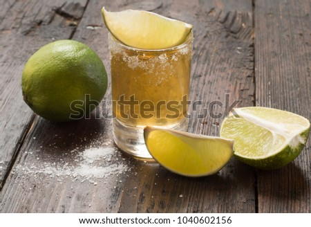 Mexican Gold Tequila with lime and salt on wooden table