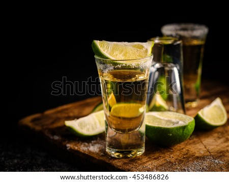 Mexican Gold Tequila with lime and salt on wooden table, Shallow depth of field.