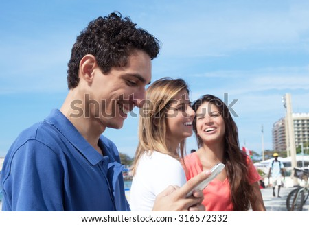 Mexican guy typing message at phone with two girlfriends - stock photo