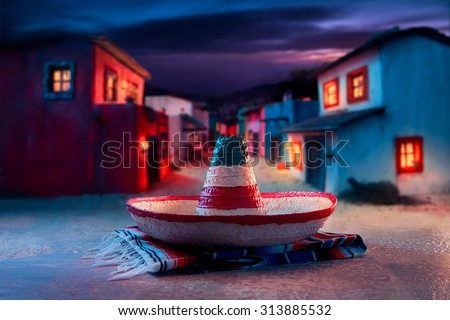 "Mexican hat ""sombrero"" on a ""serape"" in a mexican town at night - stock photo"