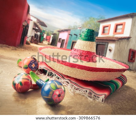 "Mexican hat ""sombrero"" with ""maracas"" on a ""serape"" in a mexican town - stock photo"