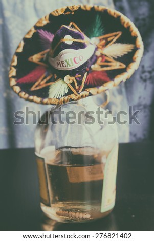 Mexican Mezcal. Mezcal from Mexico, a distilled spirit in the tequila family famous for containing a worm in the bottle. A small sombrero with the word Mexico on top. - stock photo