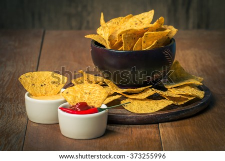 Mexican nacho chips and cheese and salsa dip in bowl on wooden background - stock photo