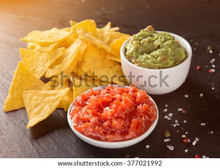Mexican nacho chips and salsa dip on black stone background - stock photo