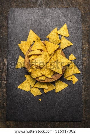 Mexican nacho in a wooden bowl on dark rustic background top view - stock photo