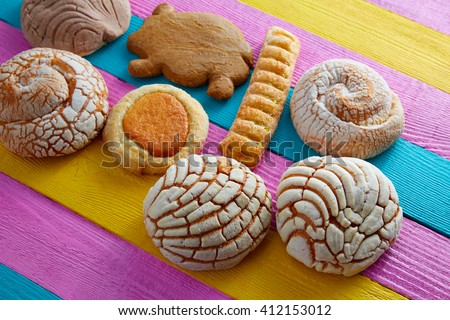 Mexican pastries concha puerquito ojo buey in a colorful wood background - stock photo